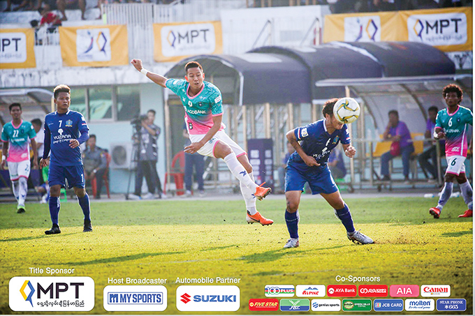 Yangon United striker Than Paing (green) kicks the ball forward during the match against Southern Myanmar yesterday at the Mawlamyine Stadium. Photo: MNL