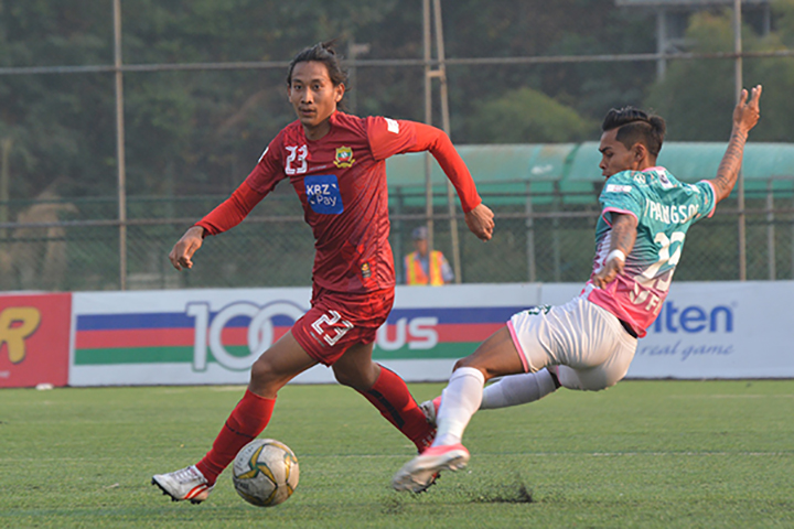 Shan United's defender Hein PhyoWai (red) passes the ball from Yangon United's Yan PaingSoe during the two team's MNL derby match at Yangon United Sports Complex on 22 February.  Photo:SUFC