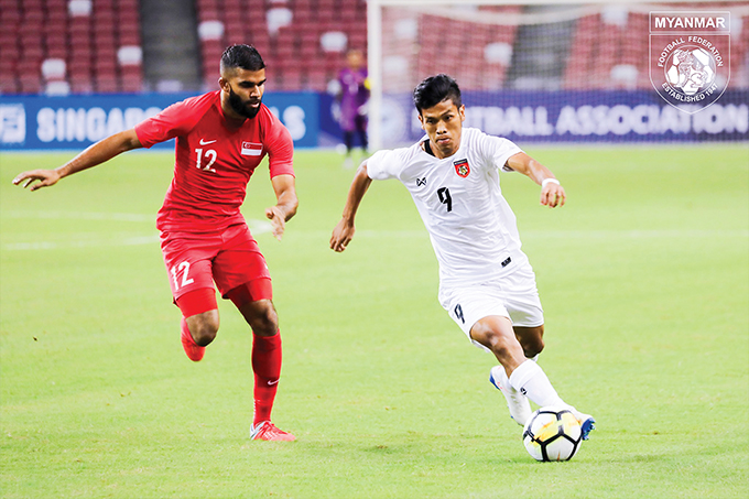 Myanmar star striker Aung Thu (No. 9) carries the ball during an international friendly match against Singapore on 11 June, 2019. Photo: MFF