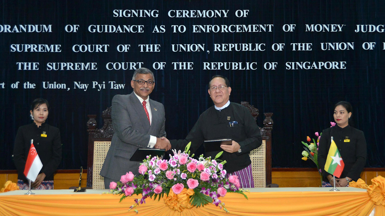 Chief Justice of the Union U Htun Htun Oo and Hon Sundaresh Menon, Singapore Supreme Court's Chief Justice exchange documents at the signing ceremony in Nay Pyi Taw yesterday.Photo: MNA