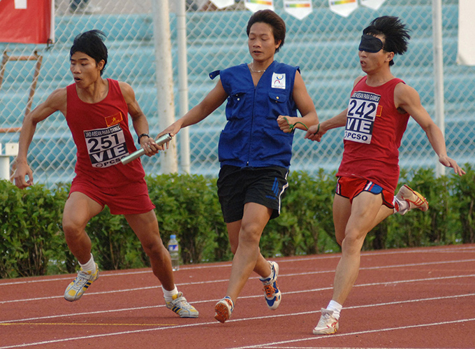 A Vietnam Para-athlete with his teammate competes during the 4x100 metre final during the 3rd Association of Southeast Asian Nations (ASEAN) Para Games in Manila 19 December 2005. Photo:  AFP