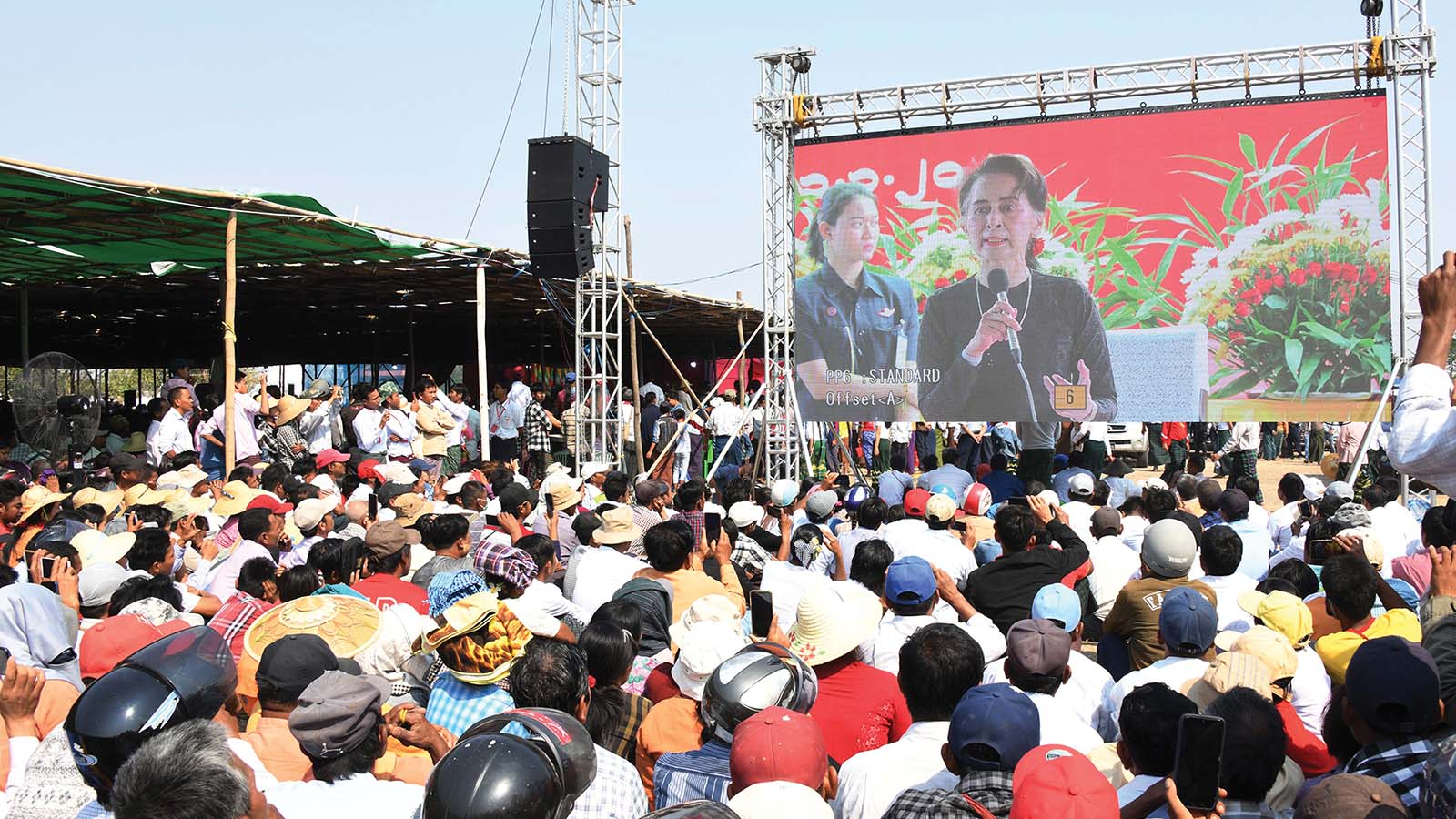 Local people gather outside the main meeting hall listening to the speech delivered by State Counsellor  Daw Aung San Suu Kyi on the LED screen in Dabayin yesterday.Photo: MNA