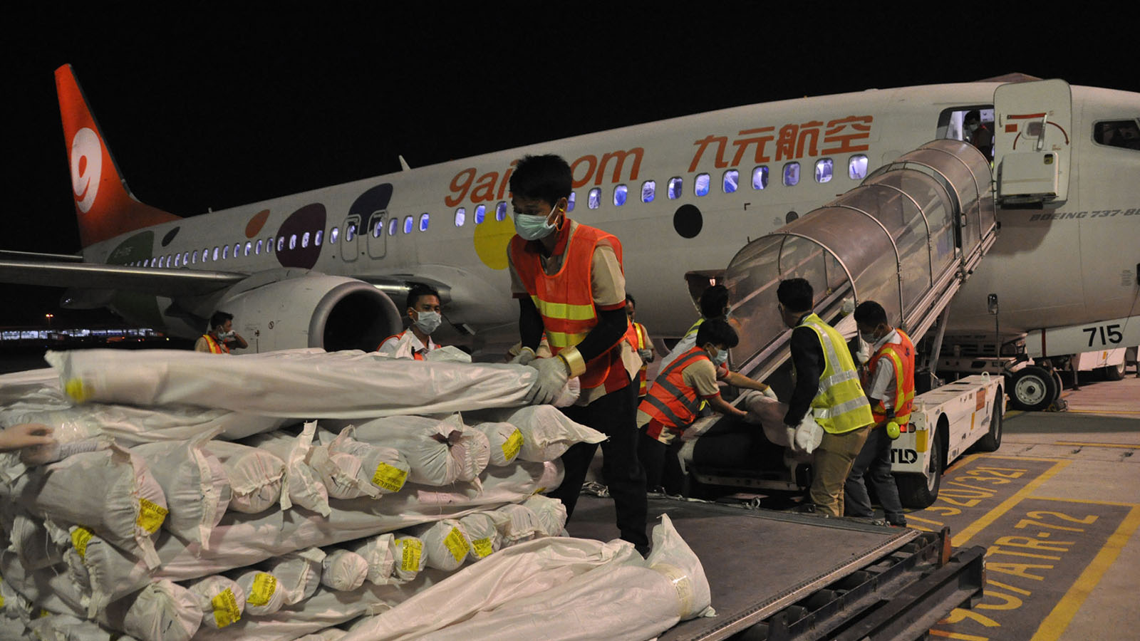 Workers conveying raw materials from the Chinese cargo plane .Photo: Than Htaik