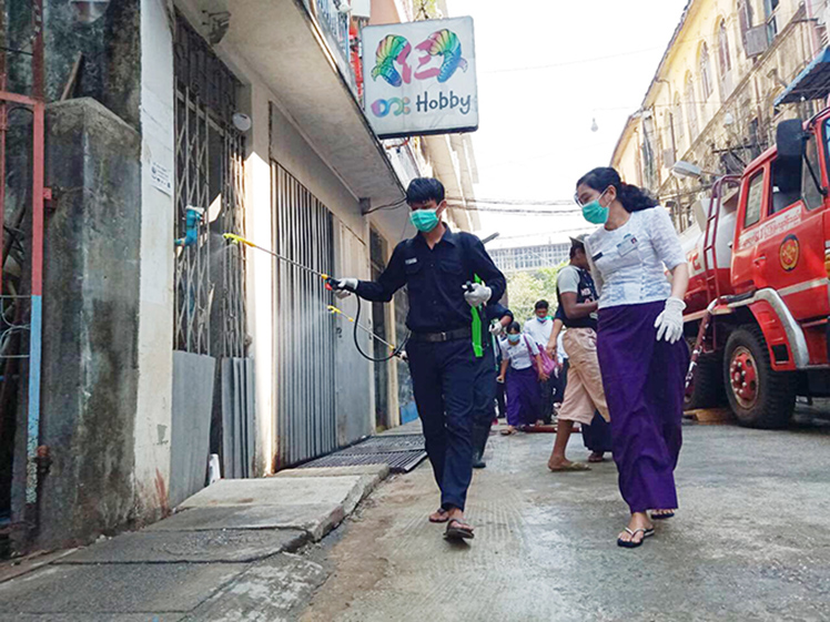 Healthcare workers spray disinfectant in Latha Townsip. Photo : Ko Ko Zaw (mna)