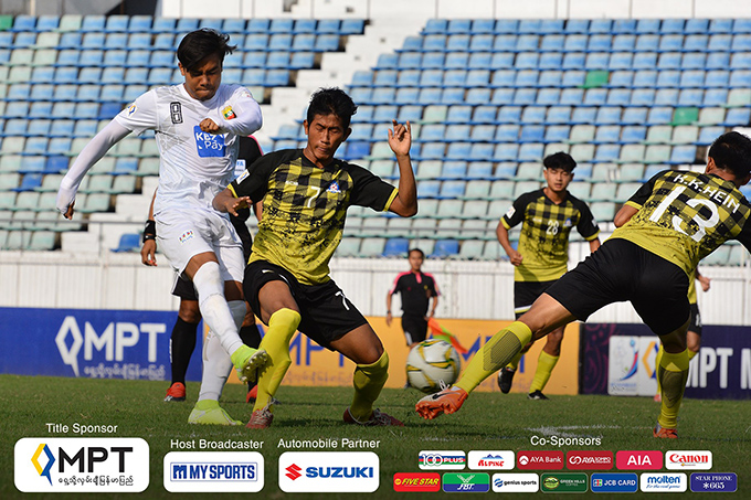 Shan United striker Zin Min Tun (white) vies for the ball against Magwe FC defenders during yesterday's Week-8 match of the Myanmar National League at the Thuwunna Stadium in Yangon. Photo: MNL