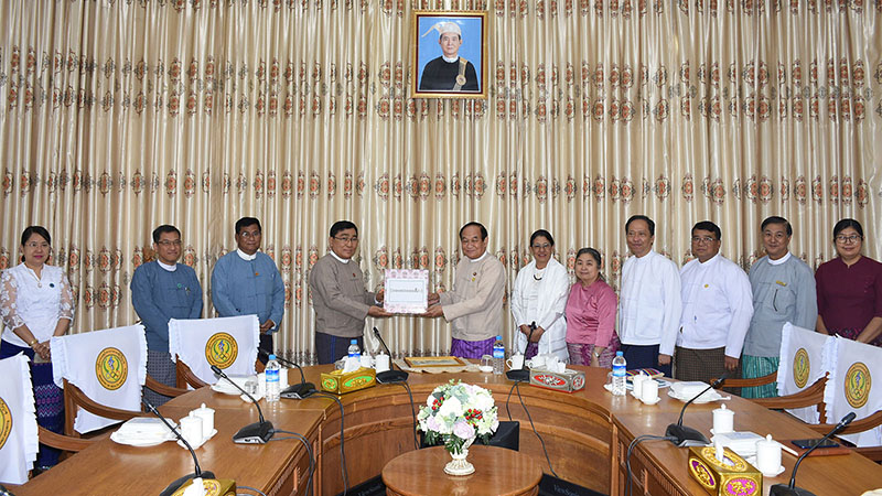 Union Minister Dr Win Myat Aye hands over K100 mln to Union Minister Dr Myint Htwe.  Photo: MNA