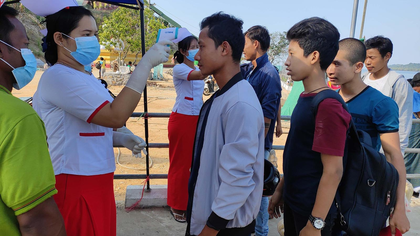 A nurse checking the body temperature of passengers at port bridges in Kyunsu Township. Photo: Sithu Aung