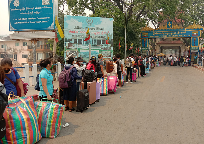 Myanmar migrant workers returning from Thailand queue at  Myanmar-Thai Friendship Bridge 1 in Tachilek, Shan State on 27 March.Photo : Yar Say
