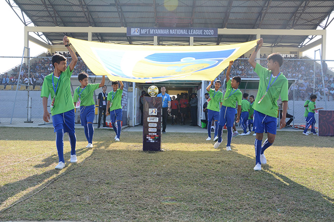Boys bring out the football flag before a Myanmar National League 2020 match. Photo: MNL