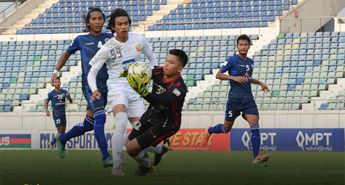 Chin United keeper Tun Aung Kyaw (black) grabs the ball kicked by Shan United's Shwe Ko (white) during their MNL Week-8 match yesterday at the Thuwunna Stadium in Yangon. Photo: MNL