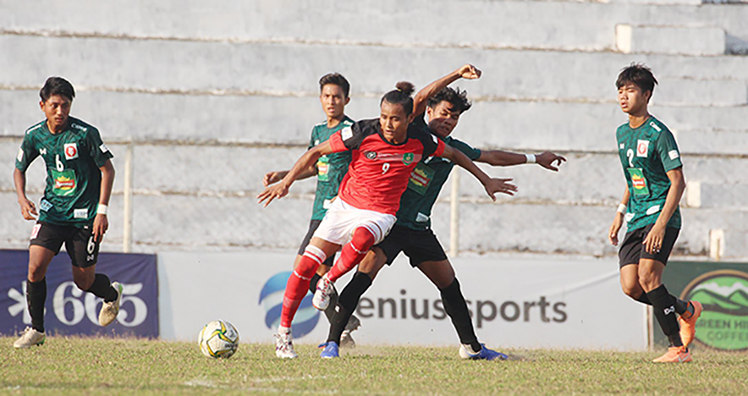 A player from Myawady FC (red) dribbles the ball past Junior Lion players during yesterday's MNL II match at Padonmar Stadium in Yangon.Photo: MNL