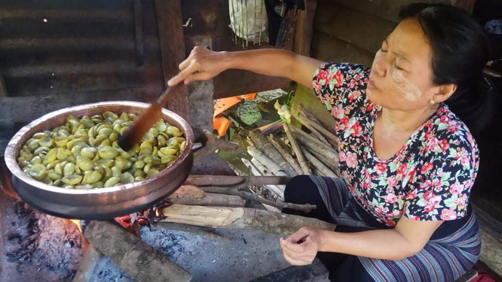 A woman cooks halved marian in the pan to make jam. Photo: Khon Winpa