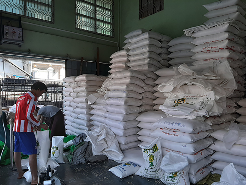 Workers packaging sacks of rice at a warehouse in Yangon.Photo : Thin Zar Hlaing