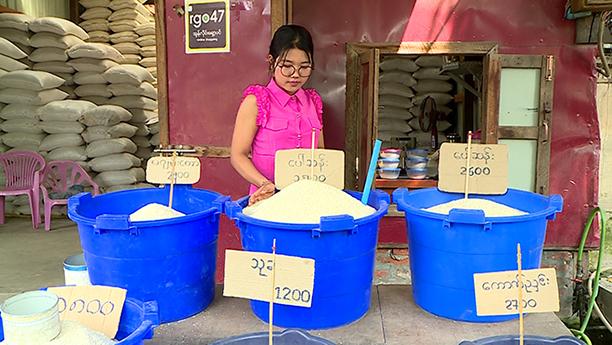 A shopkeeper selling rice at a rice shop in Mandalay.Photo: mna