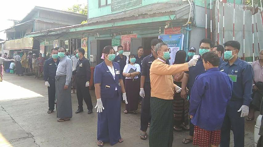 Officials measuring body temperatures of the local people in Yangon. Photo: Maung Maung Myint