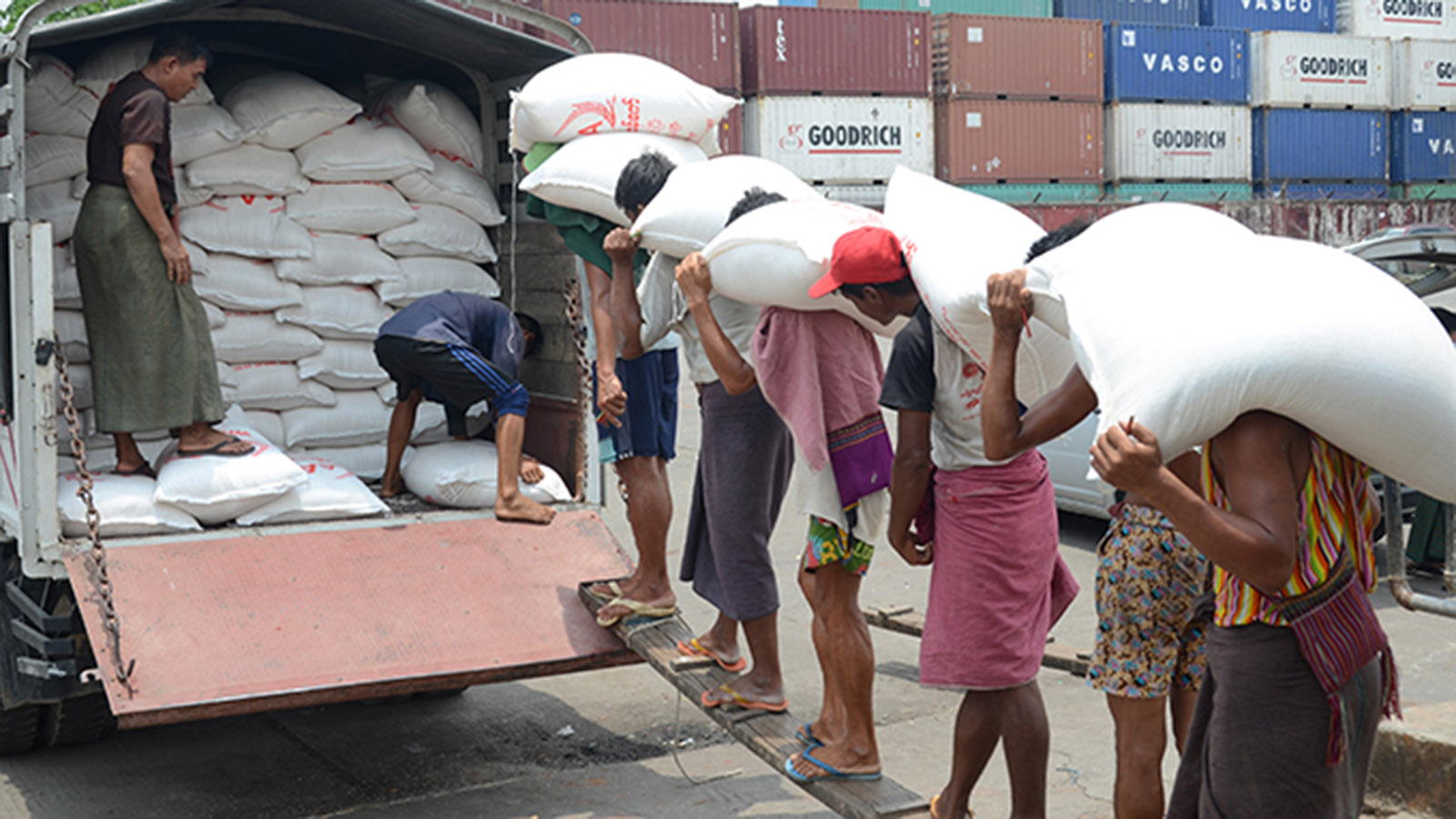 Workers carrying sacks of rice at the Botahtaung Jetty in Yangon.Photo : Phoe Khwar