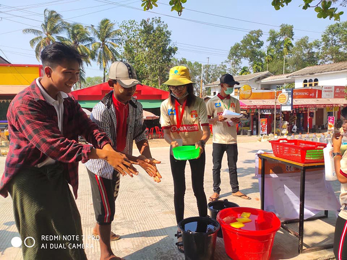 A football fan of Ayeyawady United helps two  boys wash thier hands as part of preventive measures against the Covid-19 in Pathein on 25 March. Photo: MNL