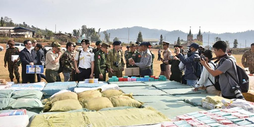 Military attaches and journalists observing the seized drugs in Kutkai yesterday.Photo: mna
