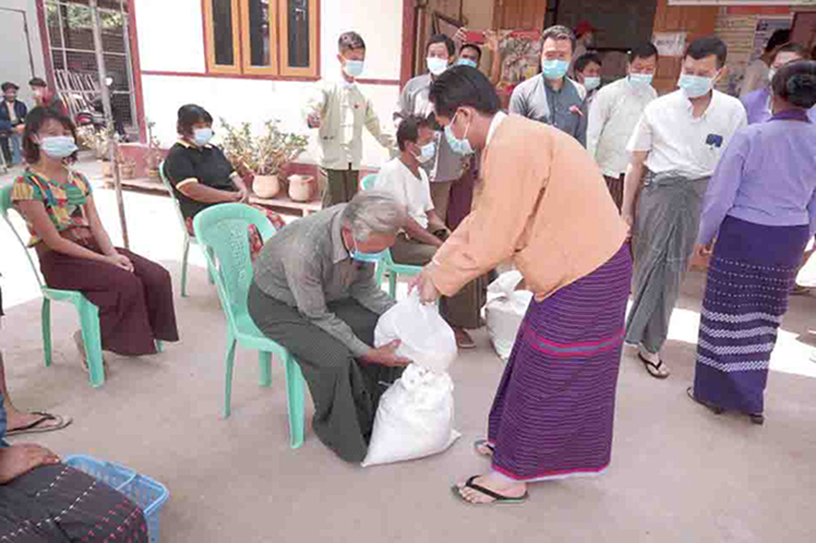 Kayah State Chief Minister U L Phaung Sho and officials hand over the foodstuffs to local people in Loikaw yesterday.Photo : Tun Lay (IPRD)