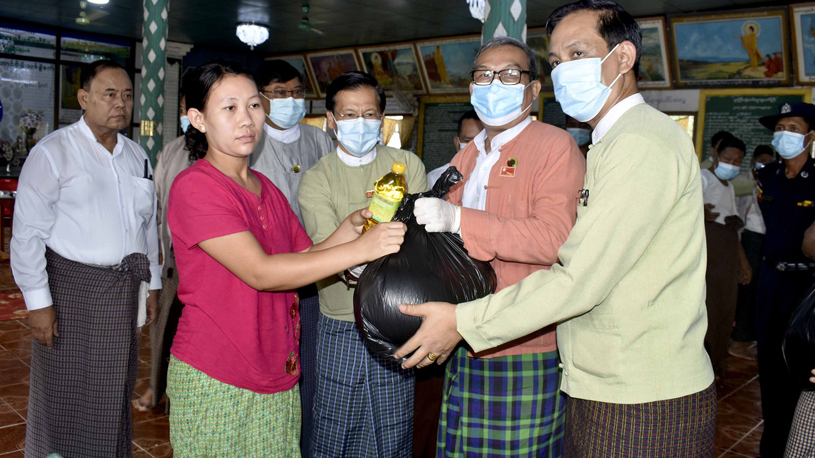 Rakhine State Chief Minister U Nyi Pu hands over household food to a local.Photo: MNA