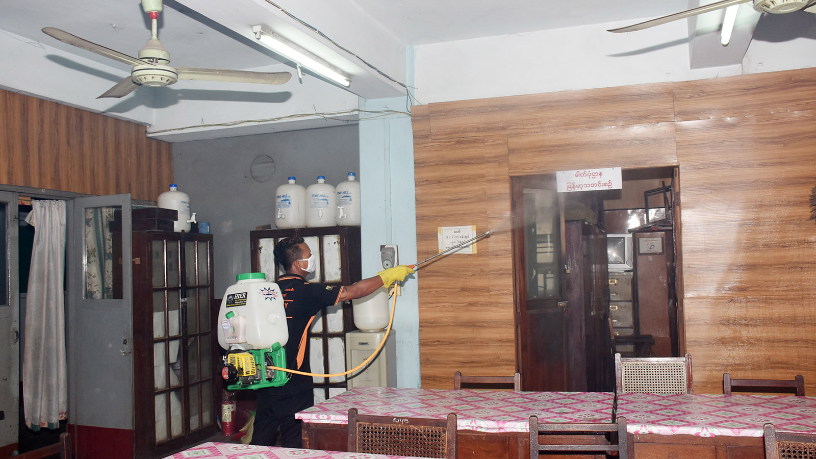 Volunteers from the Young Men Christian Association sprays disinfectants in the offices of the News and Periodicals Enterprise, Yangon, yesterday.  Photo: Zaw Min Latt (MNA)