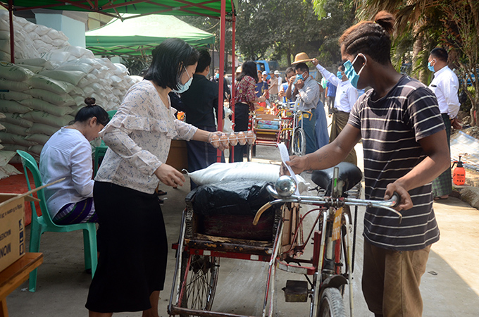 The well-wishers giving a donation of foodstuffs to the trishaw pullers in Yangon yesterday. Photo: Zaw Gyi