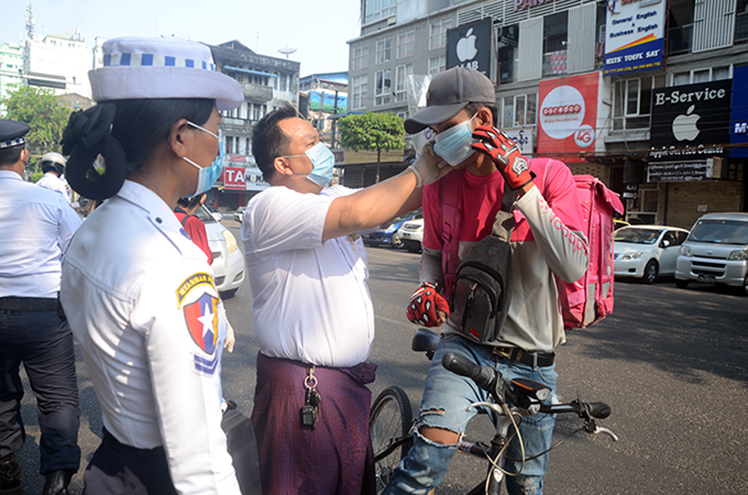 An official help a biker to wear a face mask to combat COVID-19 in Yangon.Photo: Zaw Gyi