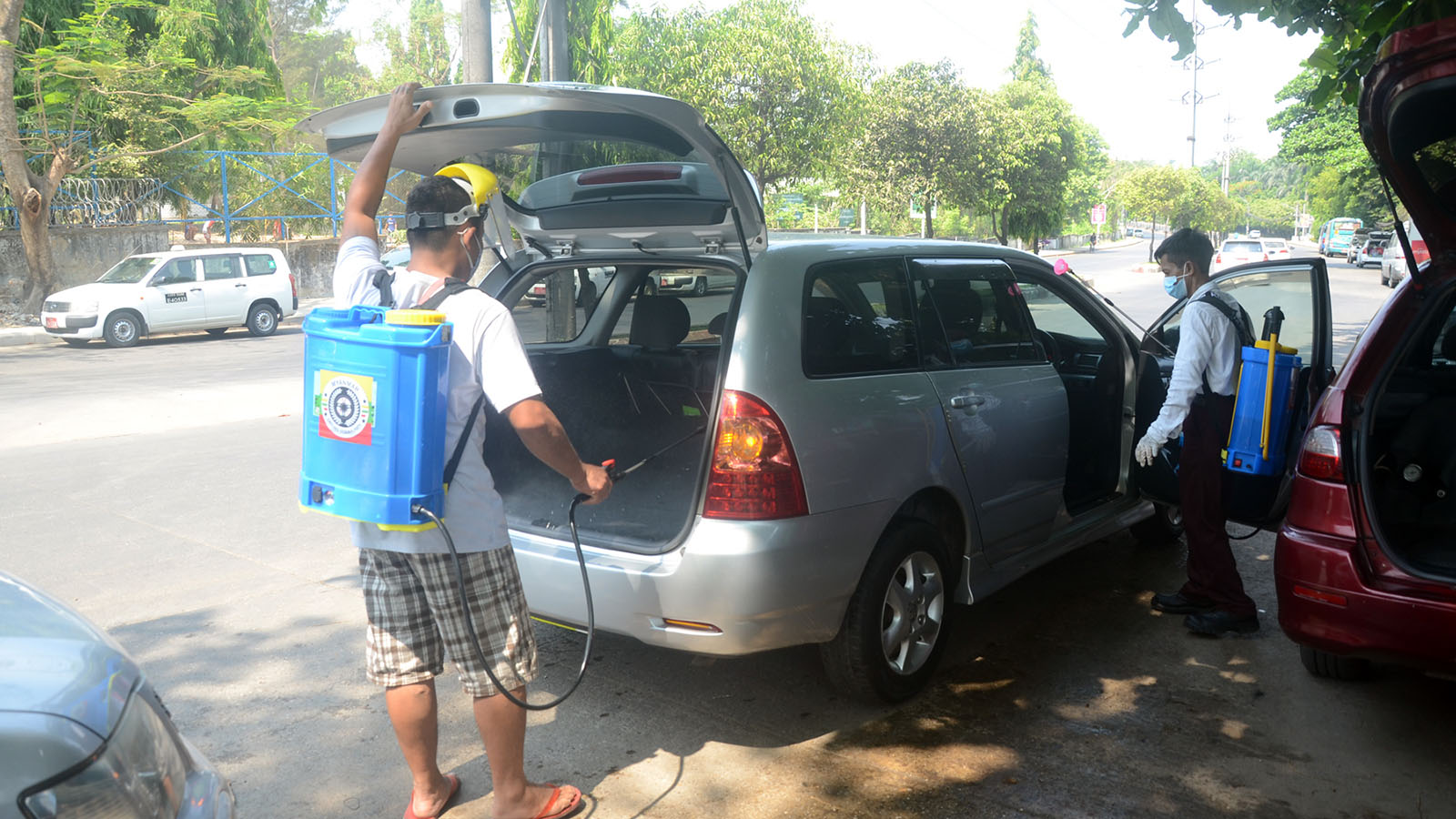 Volunteers disinfecting the vehicle in Mayangone Township, Yangon yesterday to prevent the spread of COVID-19 infection. Photo: Zaw Gyi