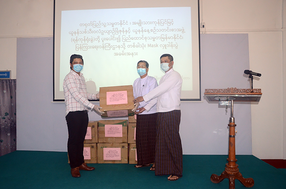 Ko Zaw Ye Aung (left) hands over face masks to Director U Thein Naing (middle) at the Film Development Centre yesterday. Photo: mna