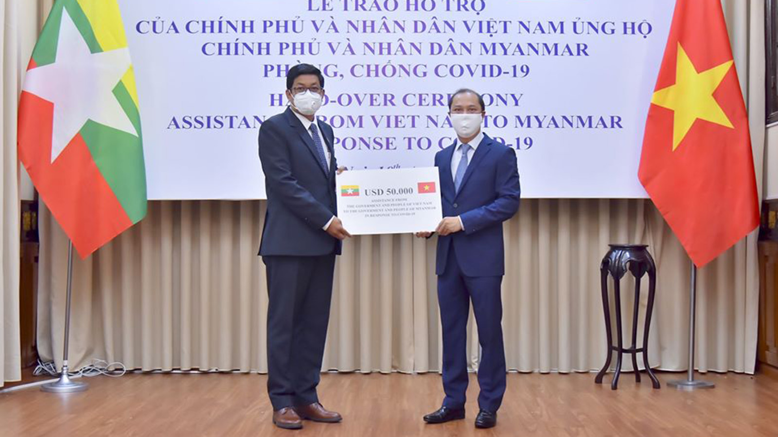 Myanmar Ambassador U Kyaw Soe Win receives the cash donation presented by Vietnamese Deputy Foreign Minister Mr Nguyen Quoc Dung in Hanoi yesterday. Photo: MOFA