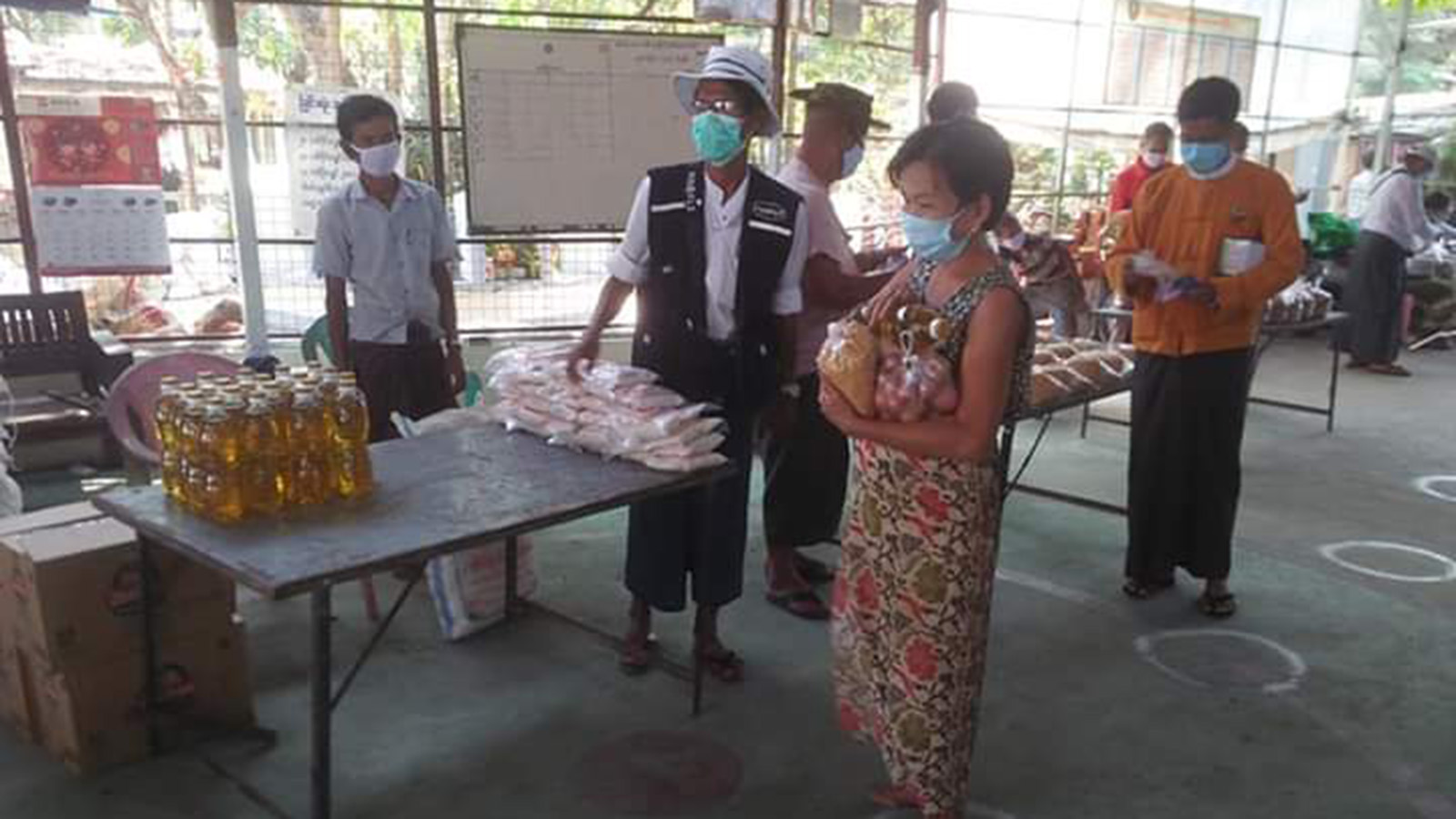 A woman receives basic food supplies from local authorites in South Okkalapa Township yesterday. Photo: Nay Htet Aung