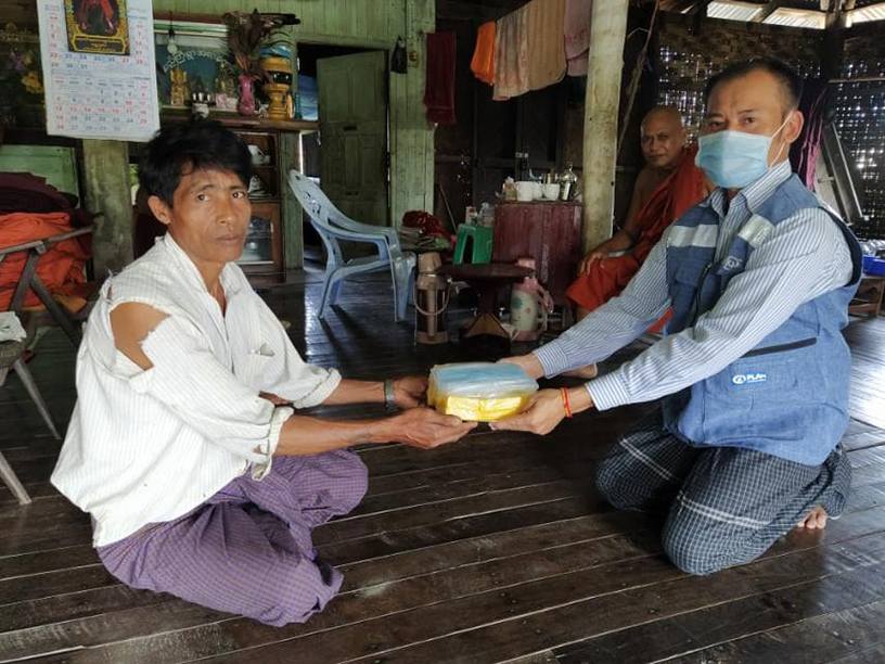 An official from Ministry of Social Welfare, Relief and Resettlement donating soap bars and face maks to a displaced person in Sittway, Rakhine State.Photo: MNA