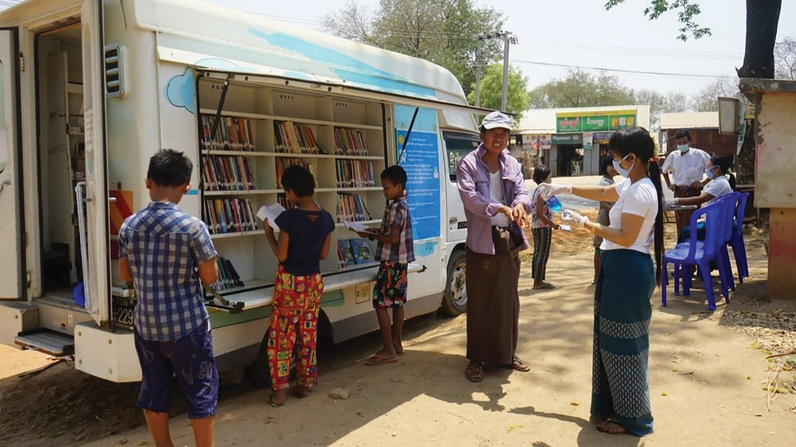 Officials demonstrate proper use of hand sanitizers, distribute pamphlets on COVID-19 and pass awareness on COVID-19 along with reading materials rental service from mobile libraries in Kwyel Min Kya Village, Natmauk Township.  photo: Thein Naing (IPRD)