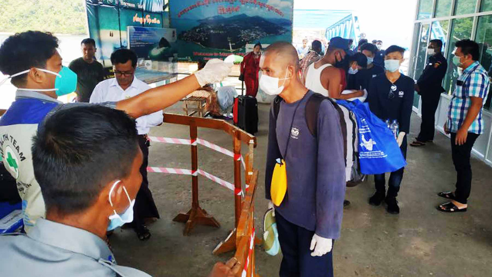 Officials testing the body temperature of the staff from the resorts and hotels on the islands in the Andaman Sea yesterday as they return Kawthoung.   Photo: Kyaw Soe