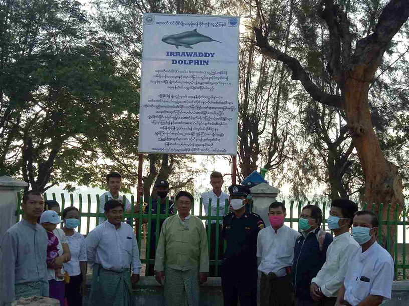 Officials from the Fisheries Department and delta locals pose for group photo after they erected a poster for conservation of Ayeyawady Dolphin. Photo: Maung Maung Myint (IPRD)