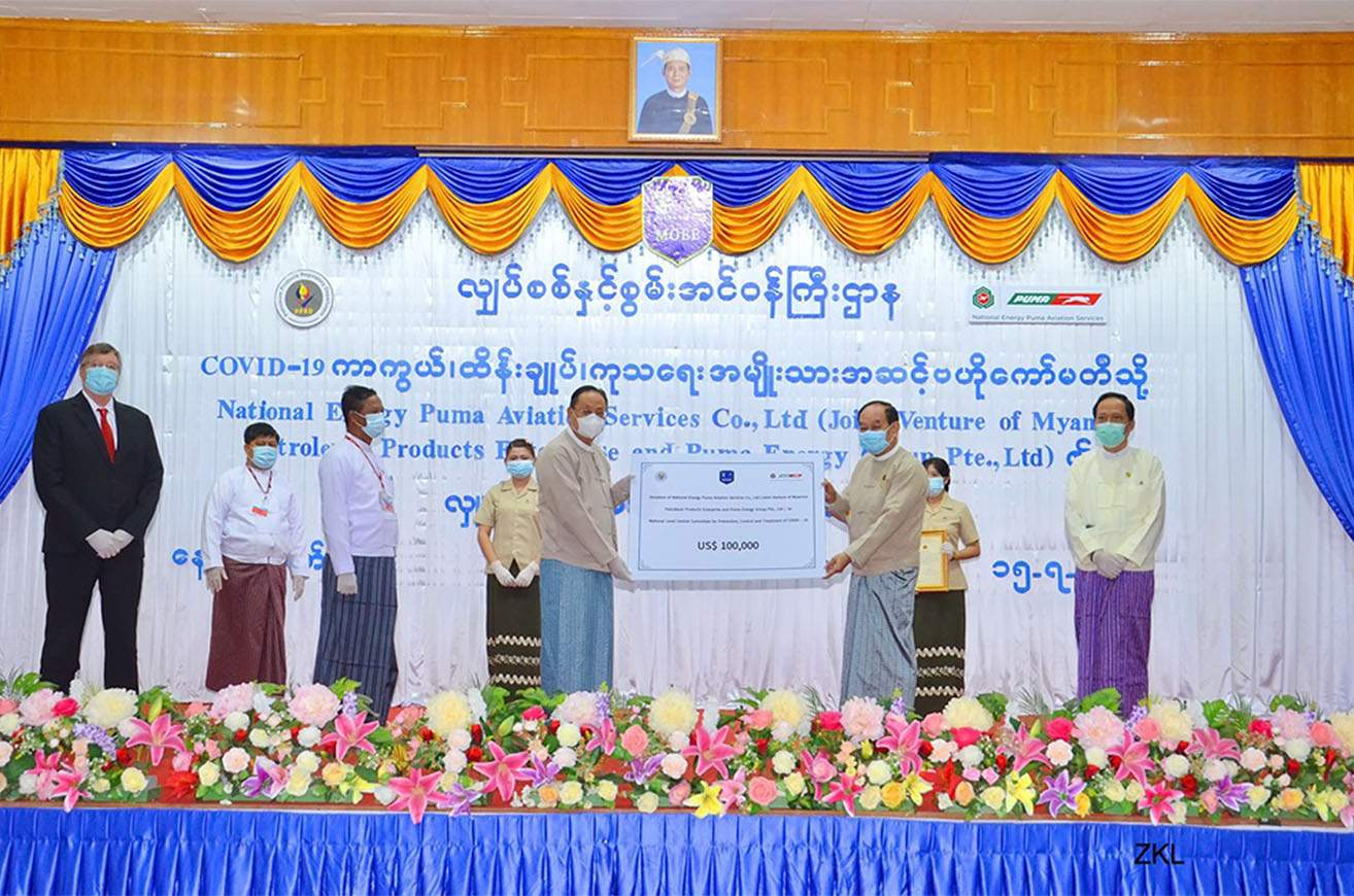 Union Minister U Win Khaing hands over US$100,000 donated by National Energy Puma Aviation Services Co., Ltd to Union Minister Dr Myint Htwe on 15 July. PHOTO: MNA