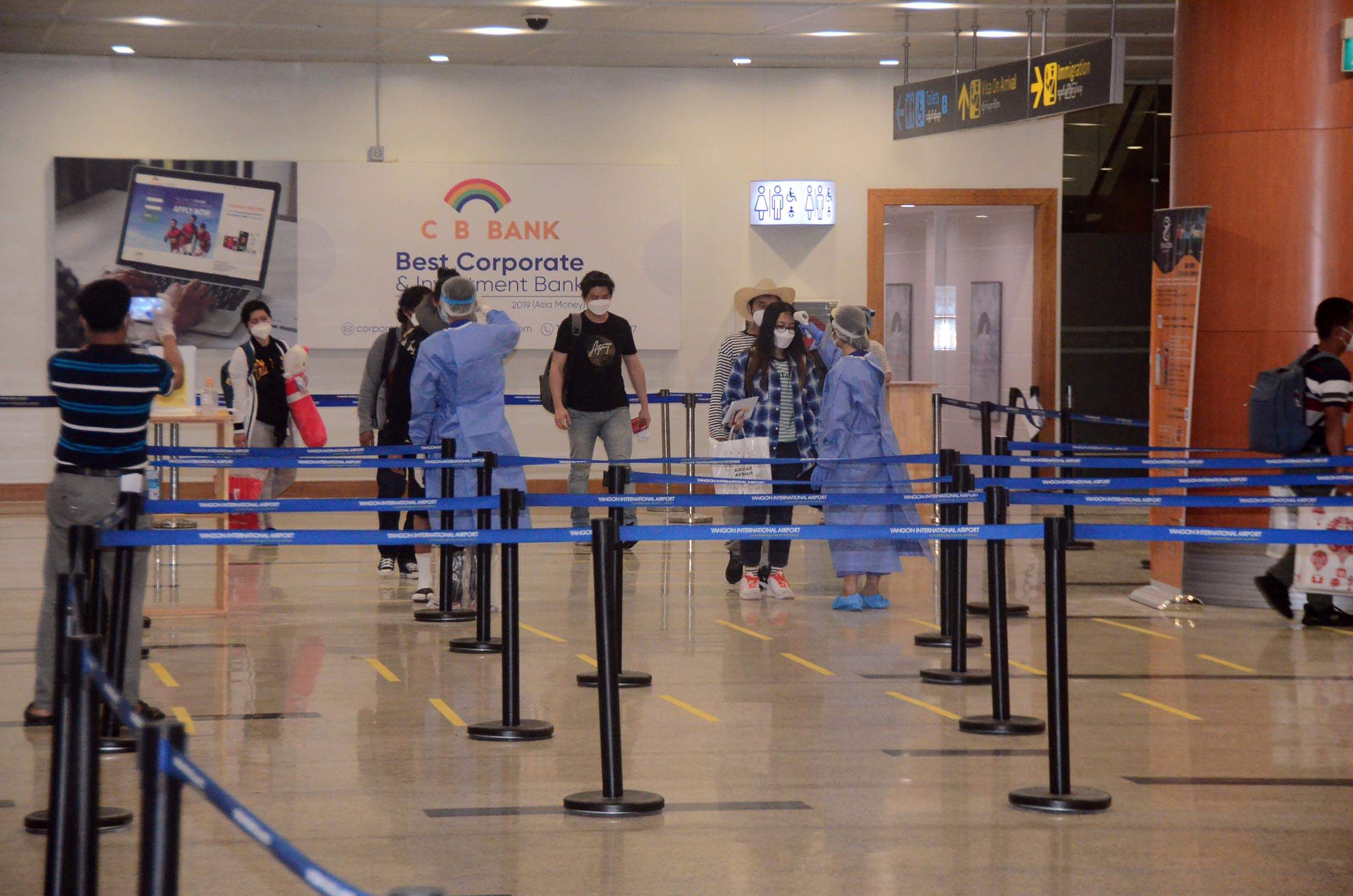 Myanmar returnees are measured for body temperatures as they arrived at Yangon International Airport on 14 July.PHOTO: MNA