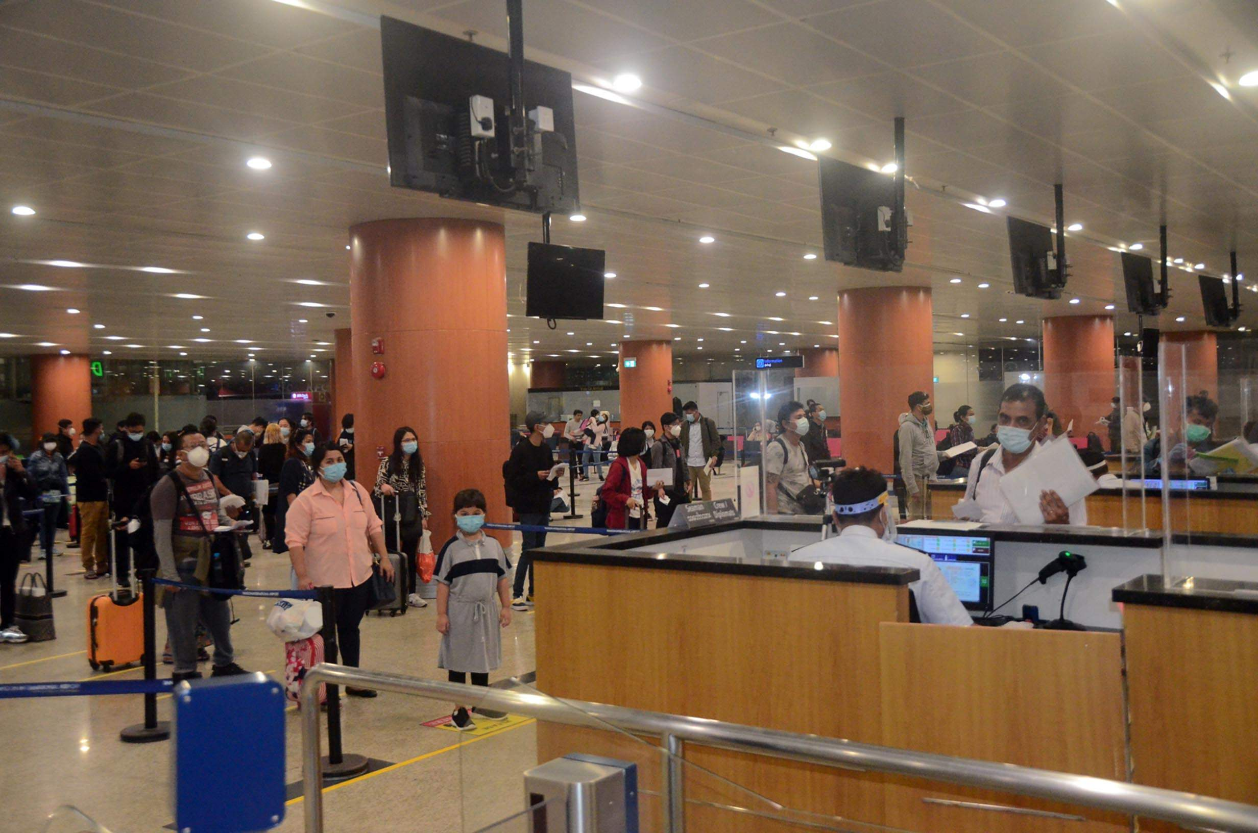 Myanmar nationals returned from Australia and Indonesia queue for immigration process at the Yangon International Airport on 20 July 2020.Photo: mna