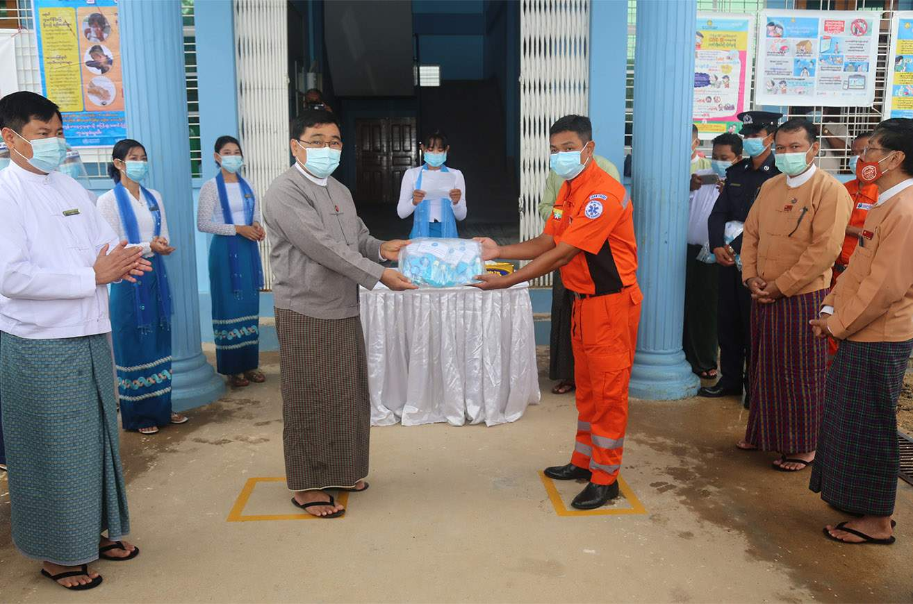 Union Minister Dr Win Myat Aye presents face masks and badges to a volunteer representative in Taninthayi Region on 12 July 2020. Photo: mna