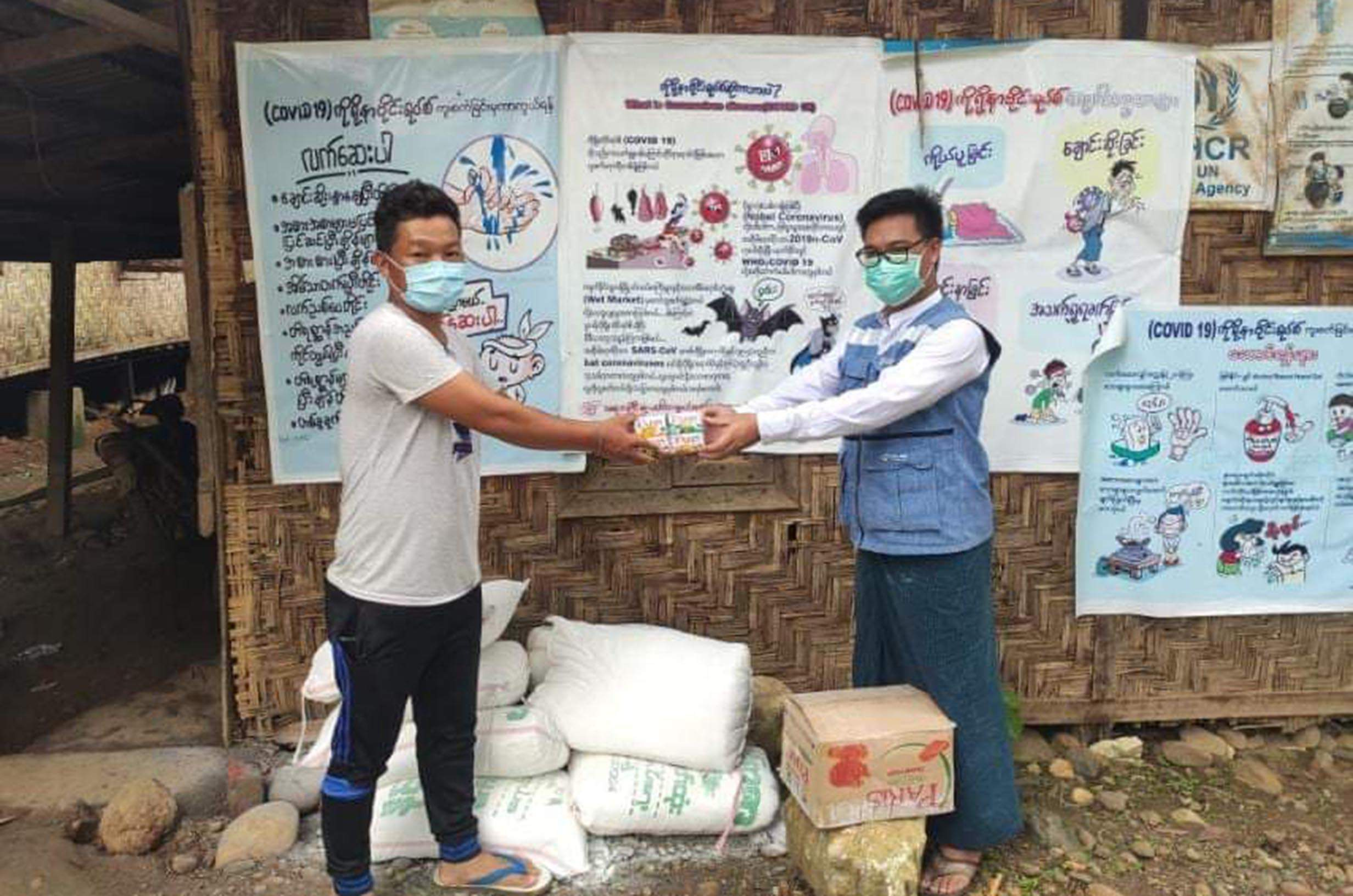 An official gives COVID-19 relief supply to an internally displaced person  in Kachin State.  PHOTO: MNA