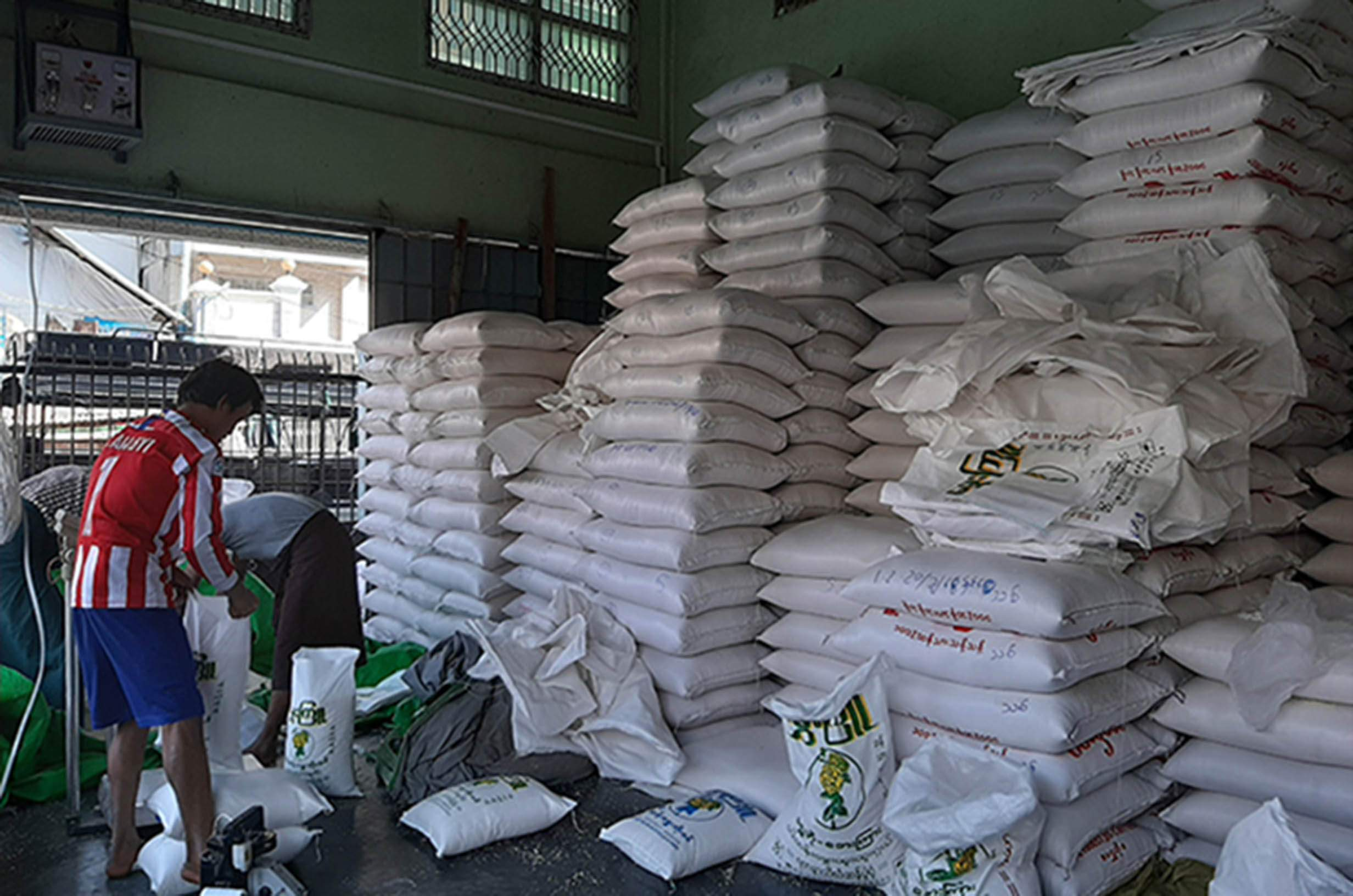 Workers bagging rice at a warehouse in Ayeyawady Region on 3 February 2020. Photo: Thin Zar Hlaing
