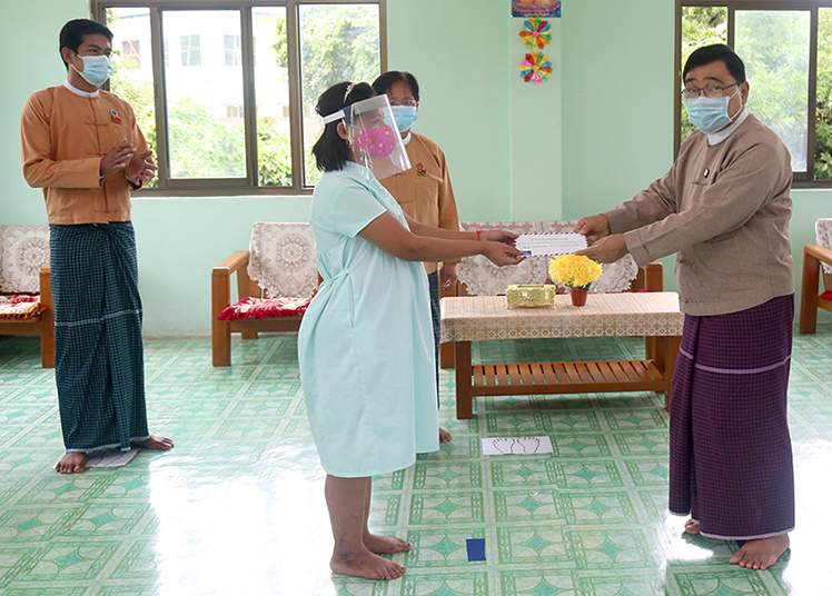 Union Minister Dr Win Myat Aye provides cash assistance to a pregnant woman in Mon State on 11 July 2020.  Photo: MNA