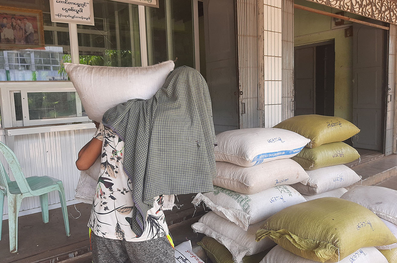 A worker carrying the sack of sesame in a warehouse in Magway.  Photo: Zayyatu (Magway)