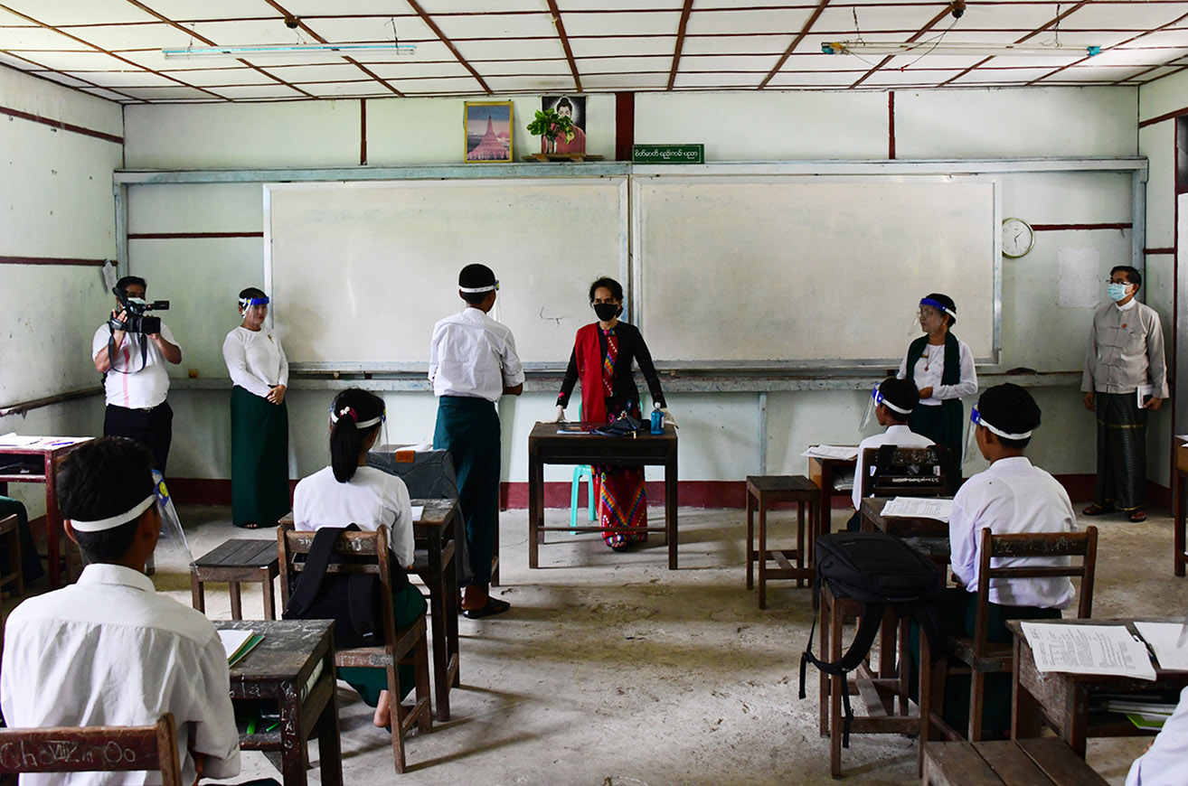 State Counsellor talks to  a student at the high school in Cocogyun Township on 6 August. PHOTO: MNA