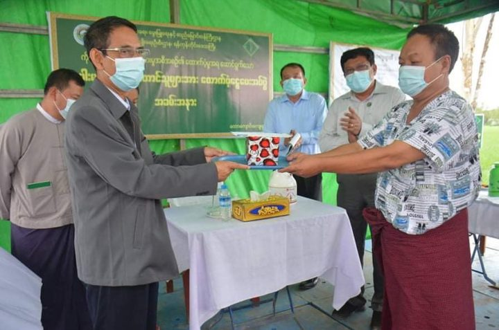Union Minister Dr Aung Thu (L) presents CERP cash assistance to a farmer in Taw Kyaung Village, Kungyangon Township in Yangon Region on 15 August 2020. Photo: MNA