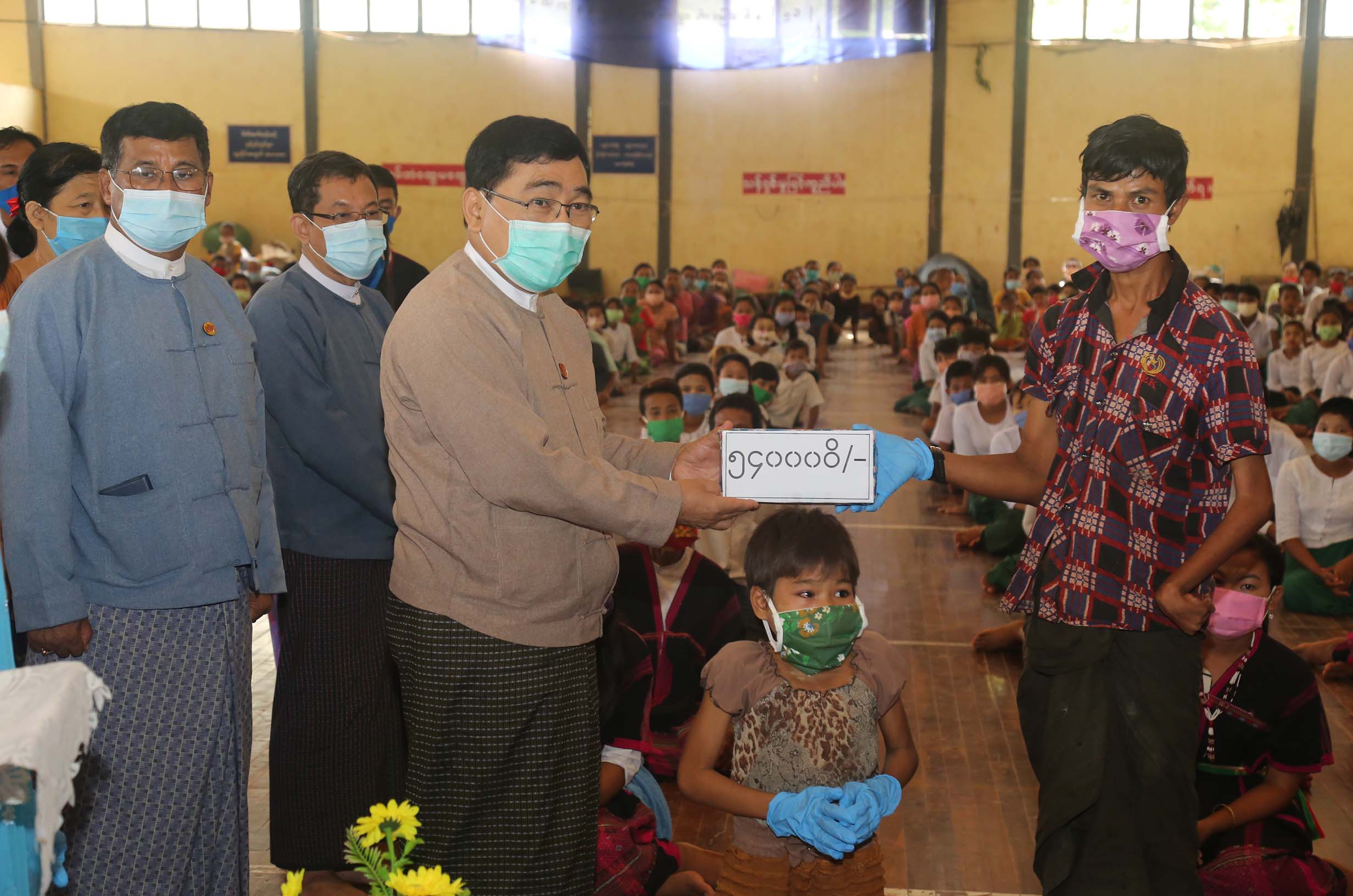 Union Minister Dr Win Myat Aye presents cash assistance for IDPs in Ann Township on 10 August. PHOTO: MNA