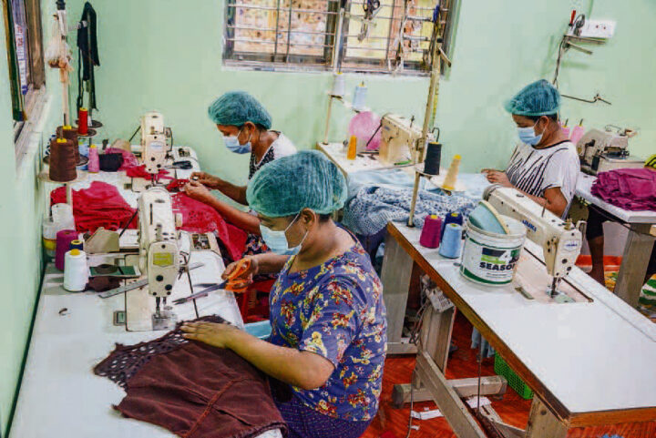 Woman sew clothes at a workplace